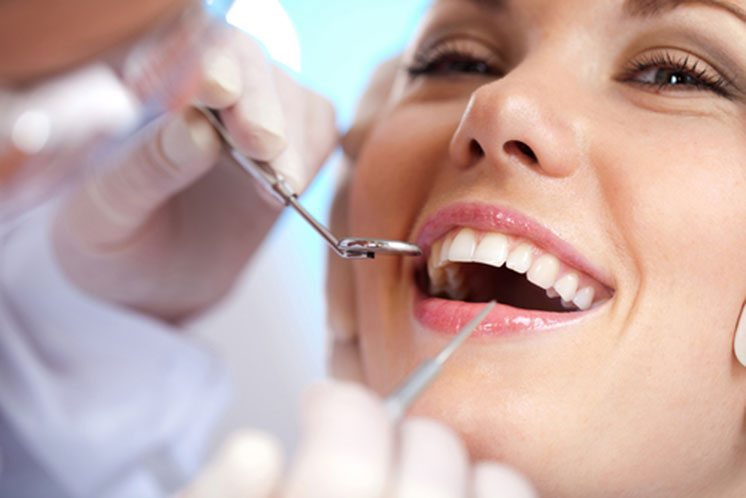 Smiling woman with dentist in mouth
